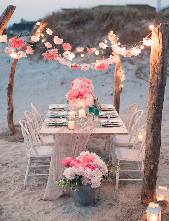 shabby chic white table, set up with plates, candles and pink flowers, six matching vintage chairs, on a white sandy beach, florida destination weddings, floral garlands and string lights