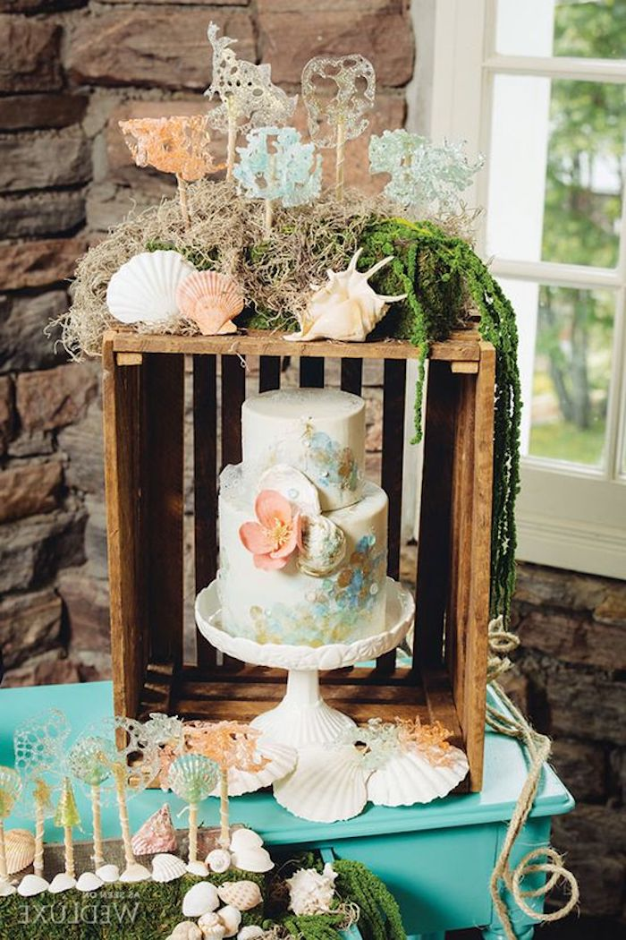 marine-inspired wedding cake, decorated with flowers, near a wooden crate, covered with grey and green moss, and pink and white seashells
