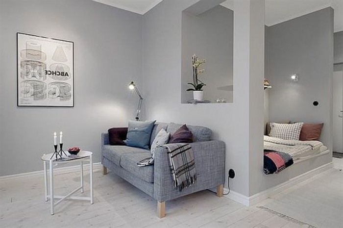 framed poster on gray wall, inside small home, with semi-detached sleeping area, studio apartment design, gray sofa and small coffee table