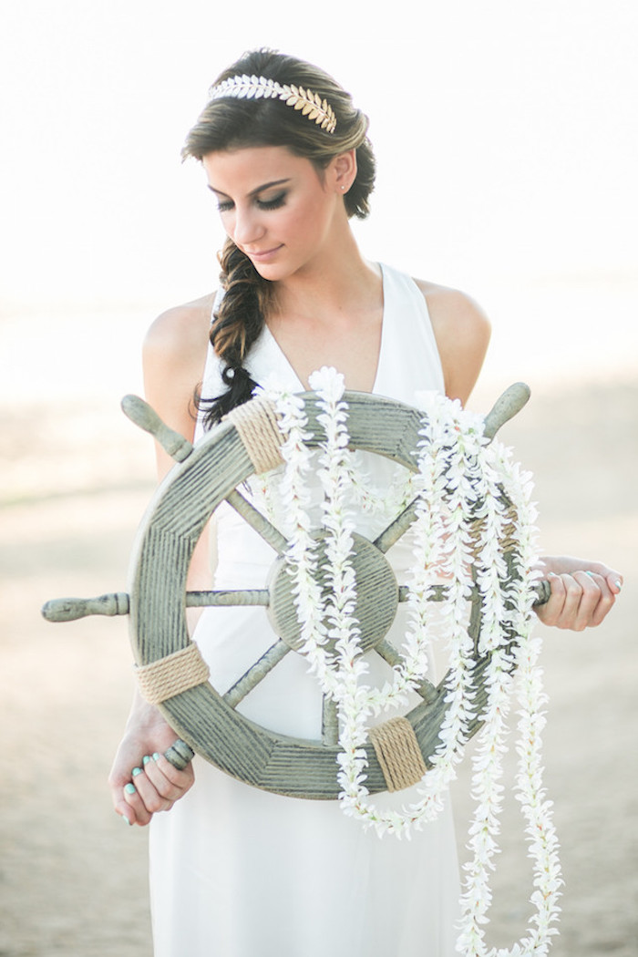 laurel-like silver hair ornament, on brunette woman with messy braid, wedding dresses for beach wedding, wearing plain white gown, and holding a ship's steering wheel, decorated with white garlands