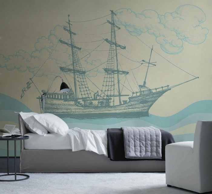 drawing of an antique ship, waves and clouds, done in different shades of blue, on a wall near a small, gray and white single bed, bedroom decorating ideas