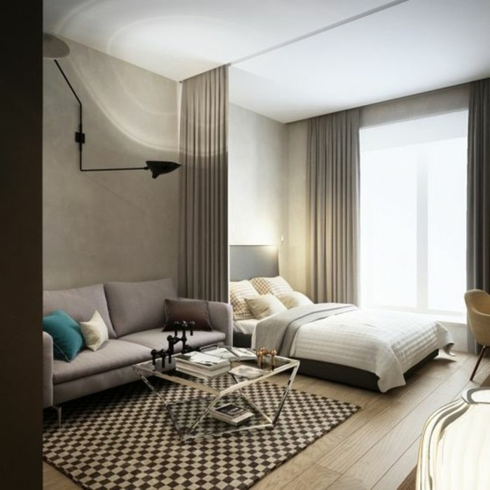 chequered rug in dark brown and cream, on light laminate floor, inside room with gray and white walls, bed with a drawn gray curtain, sofa and coffee table
