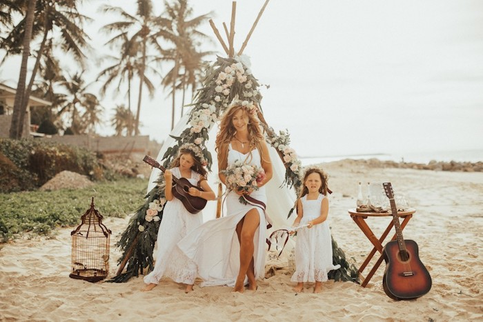 ukulele-playing young girl, next to a smiling bride, in flowy white dress, holding a bouquet, a small girl stands nearby, boho tent decorated with flowers on the beach behind them