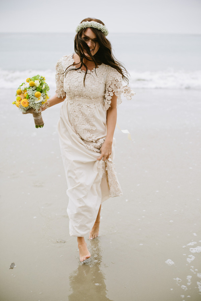 smiling brunette bride, holding a bouquet of white, yellow and green flowers, dressed in off-white embroidered gown, beach wedding dresses, walking barefoot on the shore