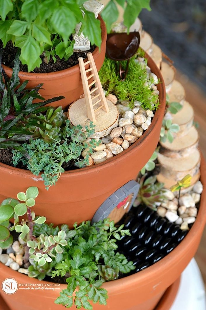 ladder of tiny size, and small door ornament, fairy garden pictures, three orange ceramic pots, stacked on top of each other, and filled with pebbles, dirt and various plants