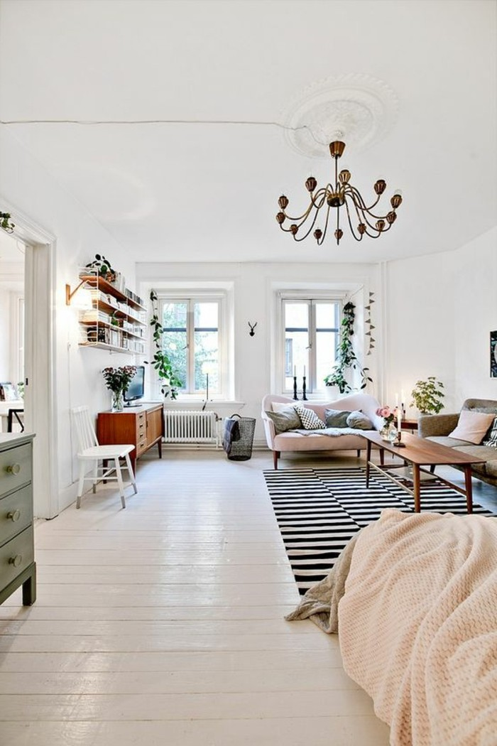 antique ornamental chandelier, hanging inside spacious room, with two windows and white wooden floor, studio apartment decorating ideas, two retro sofas and coffee table, bed and striped rug
