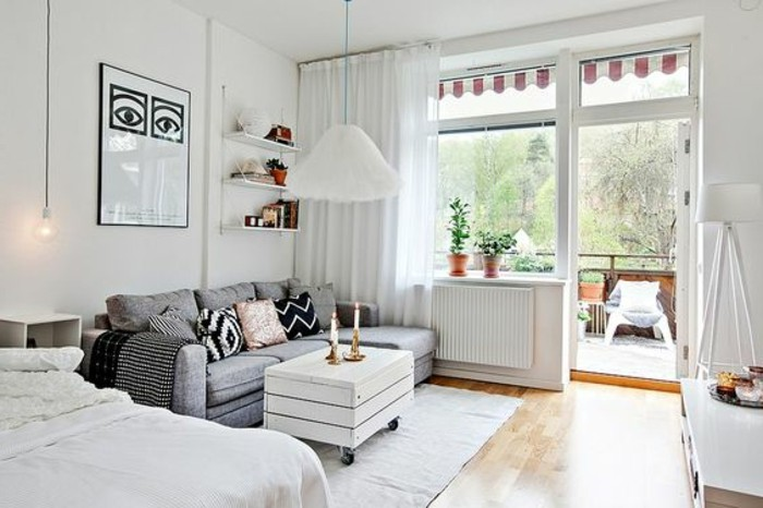open terrace attached to a bright room, white walls and sheer white curtains, pale gray sofa and white bed, small apartment ideas, laminate floor and white rustic coffee table