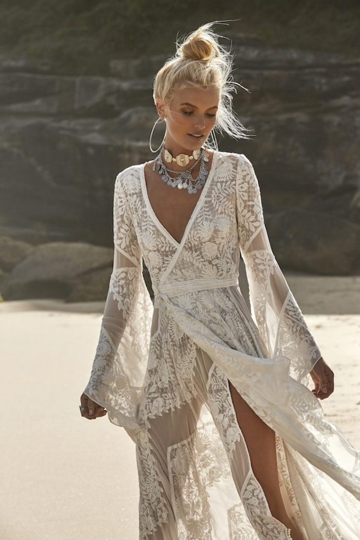 tanned blonde woman, wearing a sheer ivory-colored, embroidered wrap-over lace gown, casual beach wedding dresses, chunky metal jewelry and a messy top knot