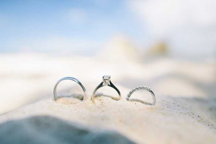 three silver rings, one thin and plain, one featuring a single diamond, and one encrusted with small stones, beach wedding ideas, placed on top of a pile of fine sand