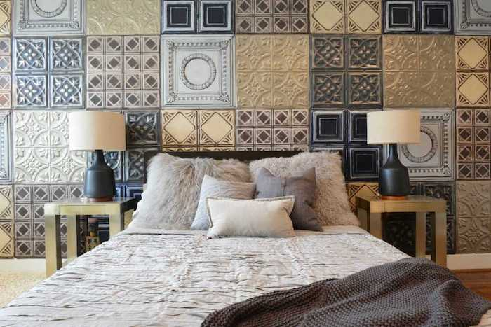 various square tiles, with different patterns and colors, covering the wall behind a double bed, two identical nightstands and lamps