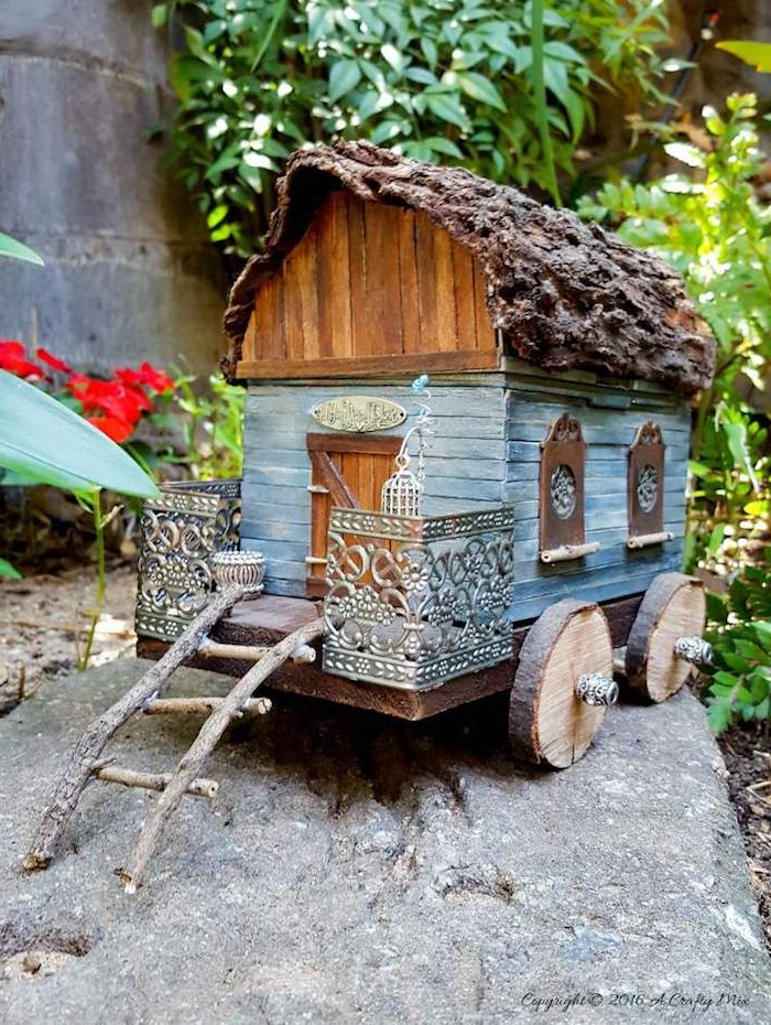 wagon or traveller's diy fairy house, made from tiny, painted wooden planks, bark and sticks, little metal ornaments, garden ion the background