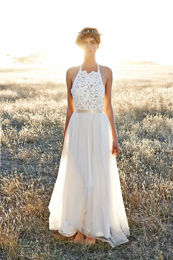 field with dry grass at sunset, slim woman standing barefoot, dressed in a long white gown, with embroidered top, and a floaty tulle skirt