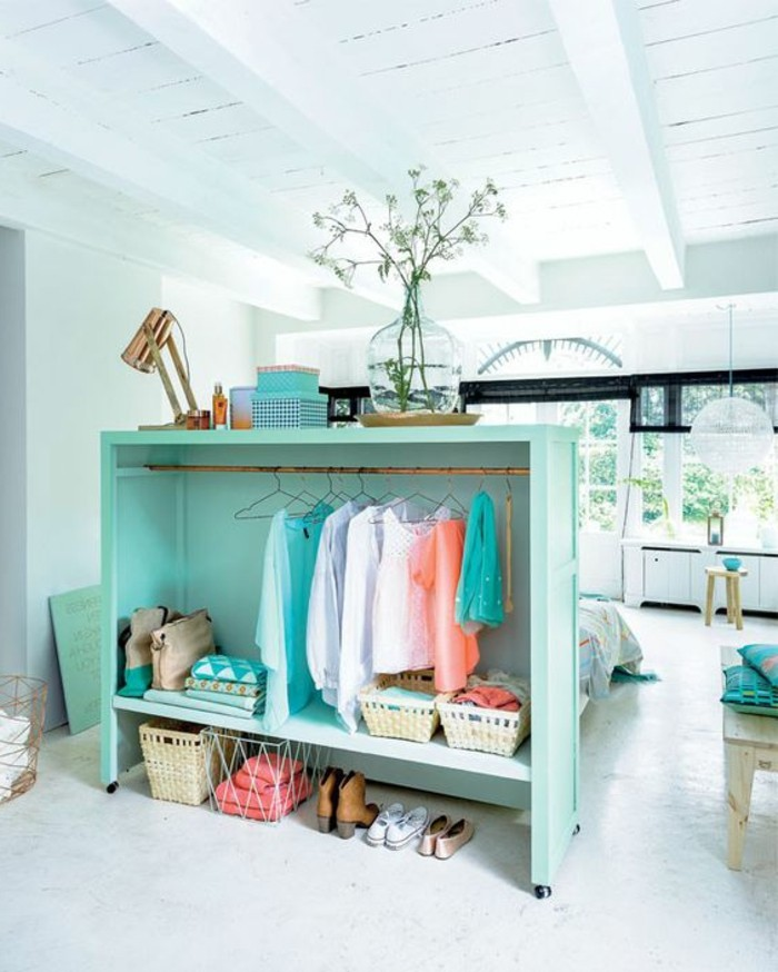 white ceiling with wooden beams, inside spacious room, with white floor, apartment design, turquoise clothes rack, with several pieces of clothing, and other items