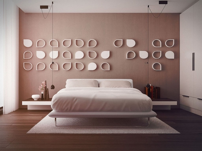 wall art décor, white hollow and solid, symmetrical tear-shaped decorations, on a pastel pink wall, in a modern minimalistic bedroom