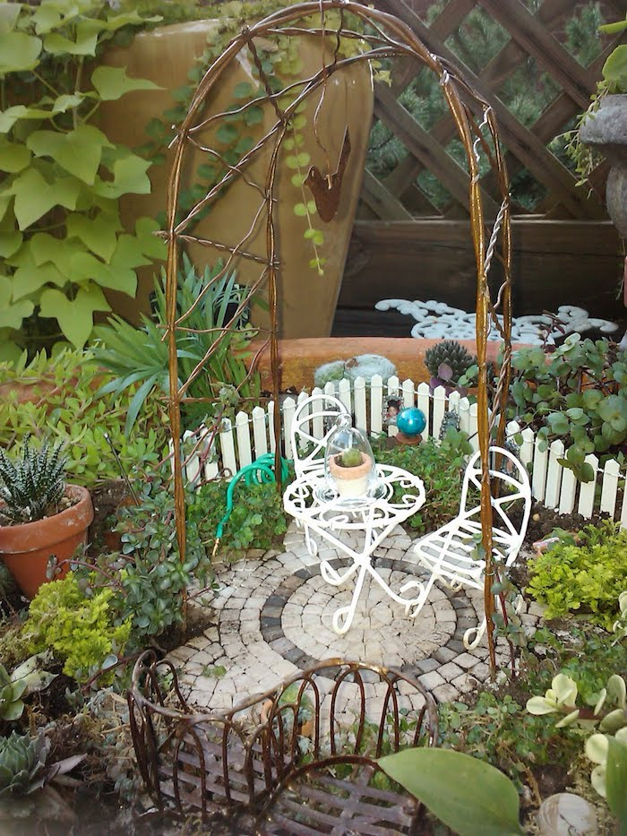 wire arch decoration, inside a miniature garden, with tiny white wrought iron table and matching chairs, tiled floor and picket fence, fairy garden pictures, various small green plants