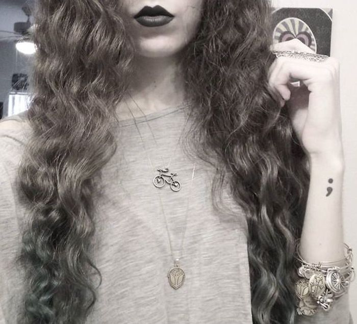 long curly hair, and dark lipstick, worn by woman with lots of jewelry, and a semicolon tattoo on wrist, cropped greyscale photo