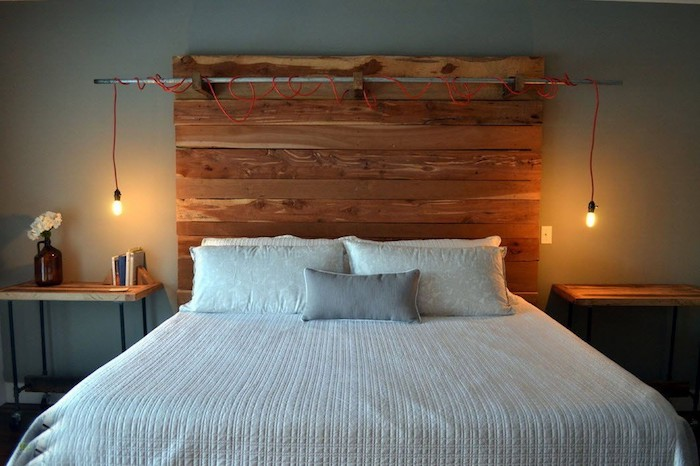 two lit light bulbs, hanging from a red cable, attached to a metal pole, bedroom design, wooden headboard made from reclaimed wood