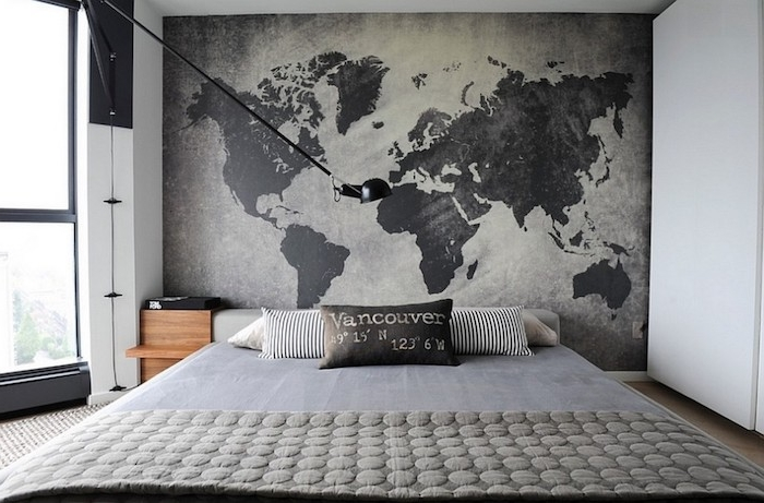large map of the world, in dark and light gray, on a wall near a simple double bed, with several cushions, bedroom design, large window on the left