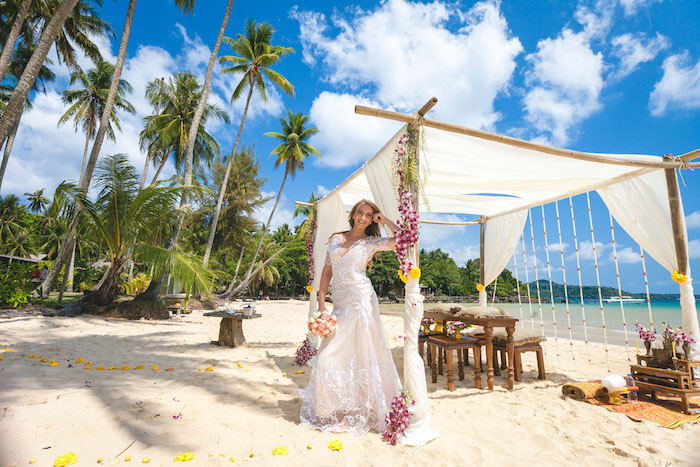 happy bride in long, cream and white embroidered wedding gown, leaning on a beach tent, decorated with flowers, beach wedding venues, palm trees and sea, wooden furniture and sand