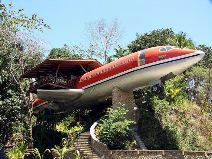 red and silver airplane, placed on stone pillars, and supported by trees, containing an adult treehouse, with wooden terrace and roof