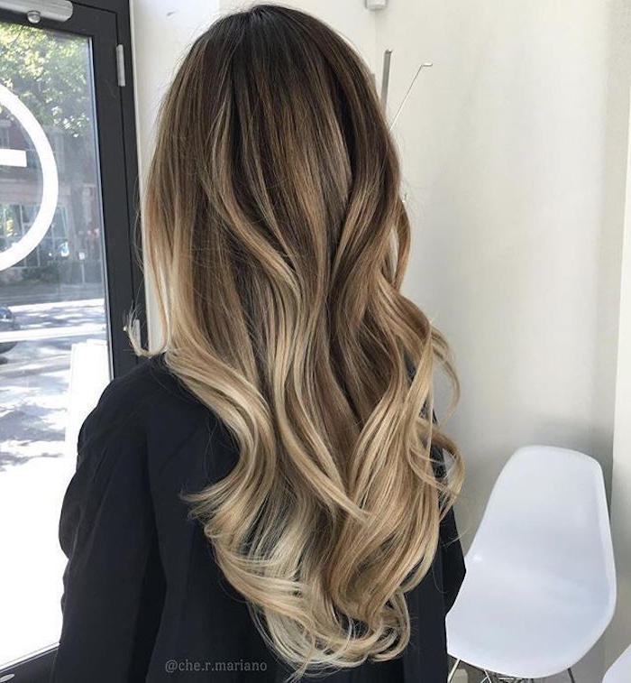 lady in black top, seen from the back, with long brunette hair, styled in loose waves, and decorated with ash blonde highlights, balayage brown hair
