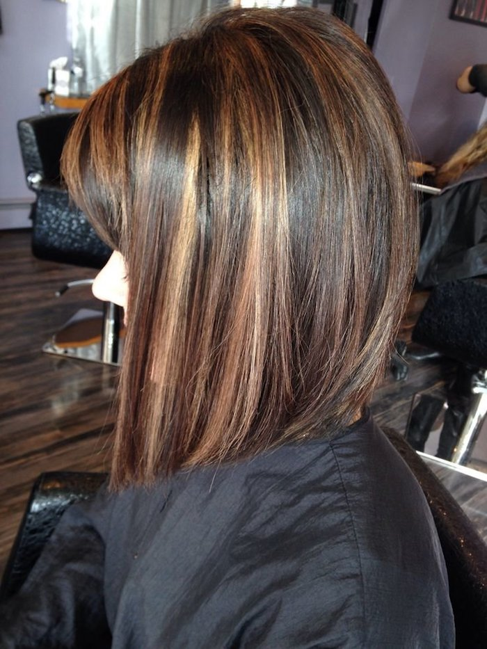 caramel highlights, on dark brunette hair, cut in a asymmetrical bob, and worn by a young woman, sitting in a hairdresser's salon