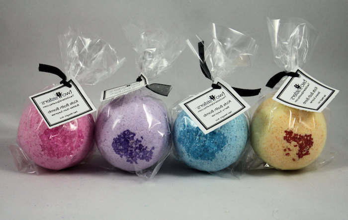 packaged bath bombs, in clear foil, with black ribbons and labels, four in total, in dark pink, light purple and blue, pale yellow with dark brown sprinkles