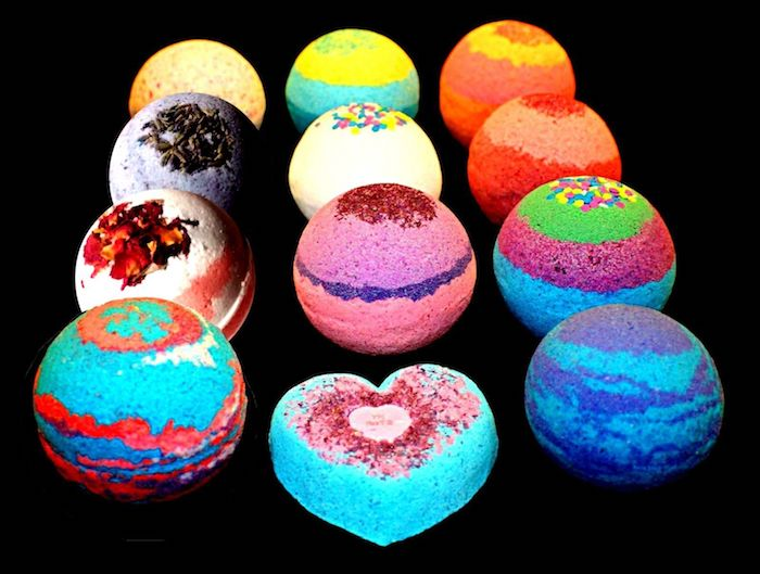 twelve different bath bombs, various colors and toppings, some are striped, one is in the shape of a heart, on a black background