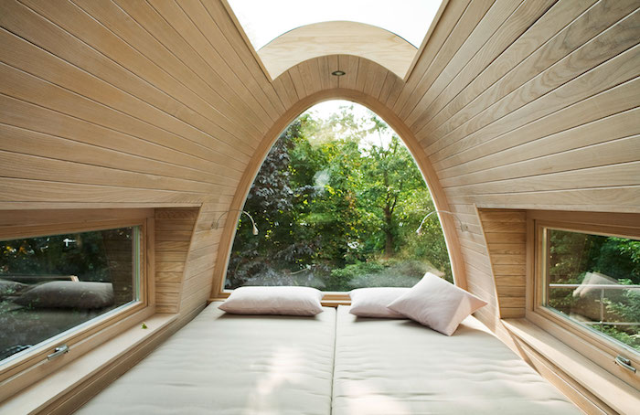 three pillows on a double bed, inside a capsule-like construction, with wood paneling, and three windows, treehouse designs