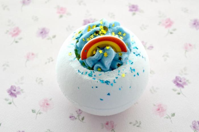rainbow bath bomb, white and blue, decorated with red and yellow bow, tiny golden star-shaped confetti, and blue sprinkles, how to use a bath bomb, placed on floral cloth