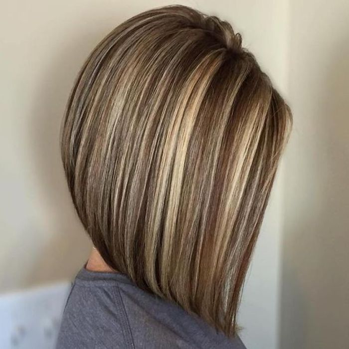asymmetrical straight bob, on medium brown hair, with light blonde contrasting highlights, worn by woman in grey top