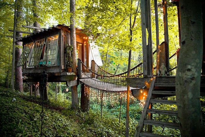 fairy lights illuminating a boho-style tree house, treehouse designs, built around several trees, and connected to a nearby structure via a bridge