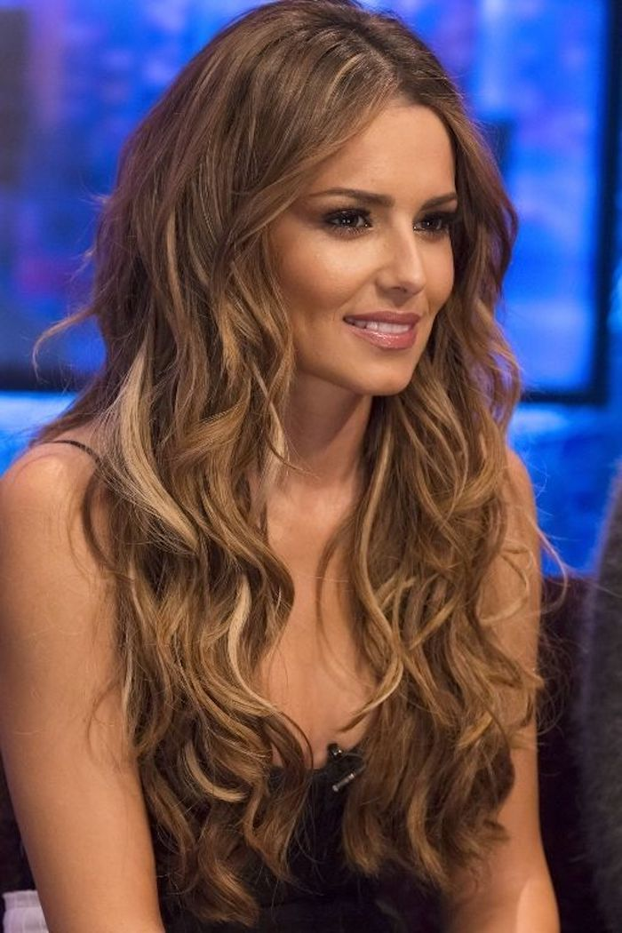 british celebrity cheryl cole, with long brown and blonde hair, styled in loose waves, decorated with highlights, she's wearing a black top and smiling