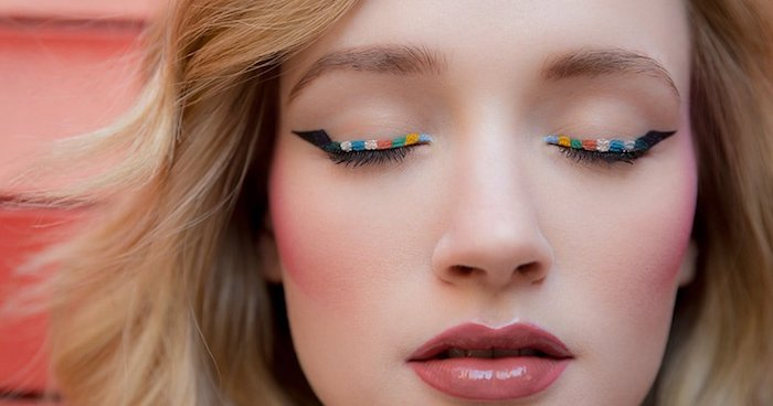 makeup ideas, glossy pastel red lipstick, strong pink blush, and multicolored eyeliner, worn by pale blonde woman, with closed eyes