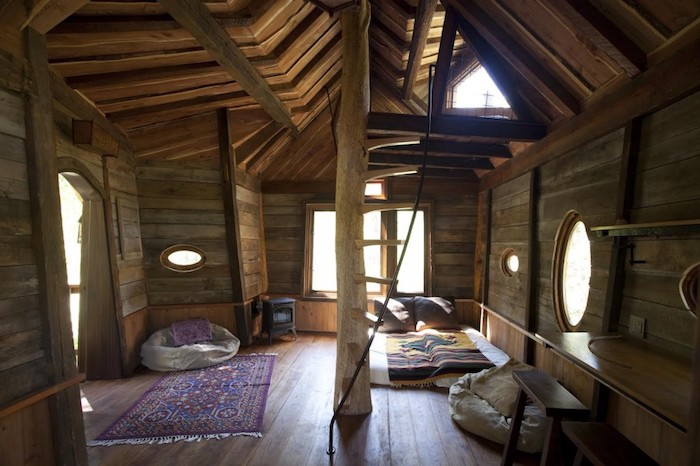 bean bag chairs, ornamental carpet and a bed, inside a boho-style tree house, with several windows, and ceiling with wooden beams