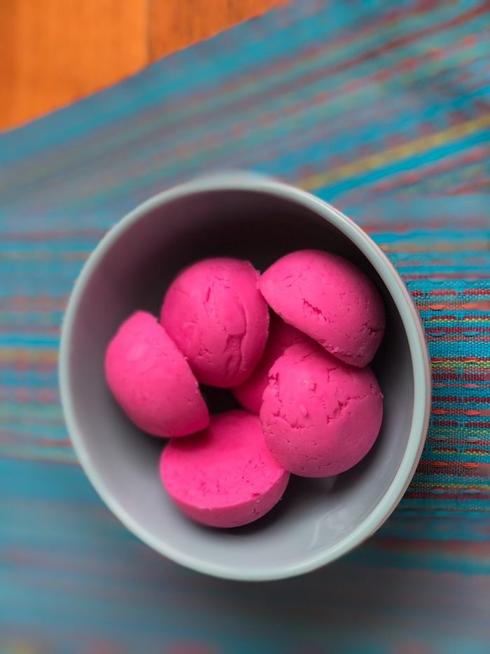 hot pink bath melts, shaped like half spheres, and placed in a pale grey ceramic bowl, on a striped multicolored cloth