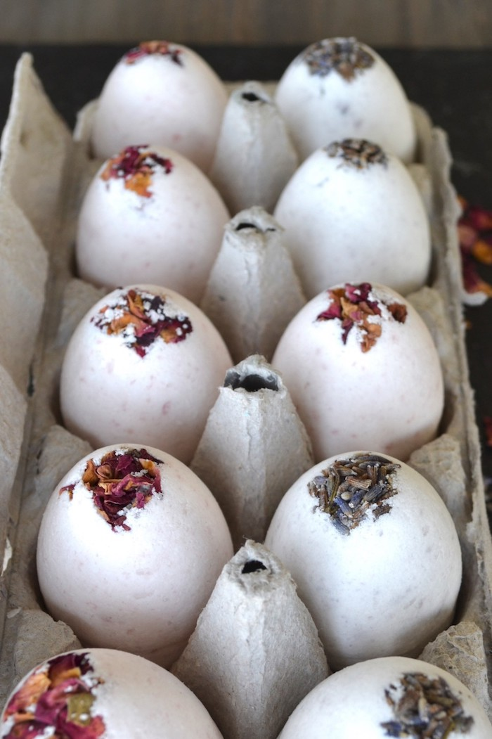 ten egg shaped bath bombs, decorated with dried rose and lavender petals on top, placed inside a grey cardboard box