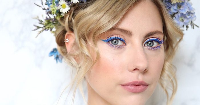 blue eyeliner worn by green-eyed woman, with nude pink lipstick, and soft blush, makeup looks, blonde hair tied up, and decorated with various flowers