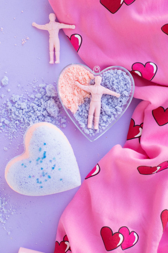 tiny man figurine, in pale pink, placed on top of lumpy powder, in peach and violet, inside a plastic heart, bath fizzies idea