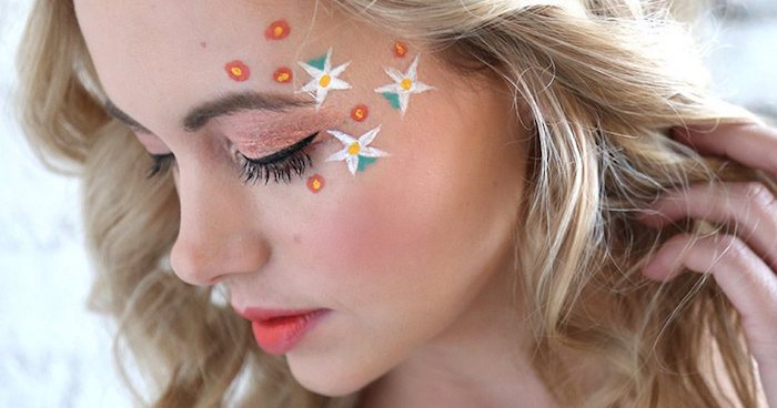tiny red and yellow flowers, and bigger white yellow and green blossoms, painted on a girl's face, cute makeup looks, pale pink eyeshadow, black eyeliner and pastel red lipstick