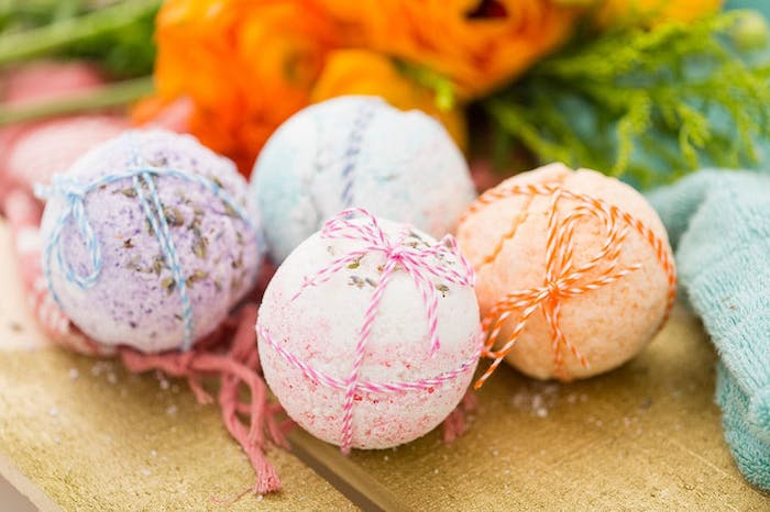 set of four bath balls, in pale purple, light pink and blue, and pale orange, placed on a wooden surface, and decorated with striped string, in corresponding colors