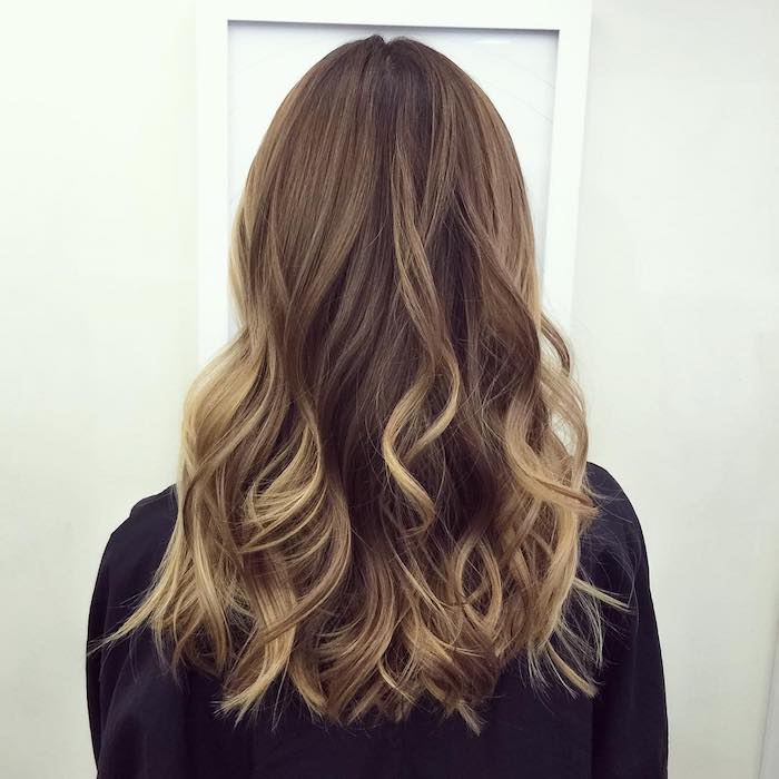 white door and off-white wall, faced by woman with medium length wavy hair, dark blonde balayage brown hair, black long-sleeved top