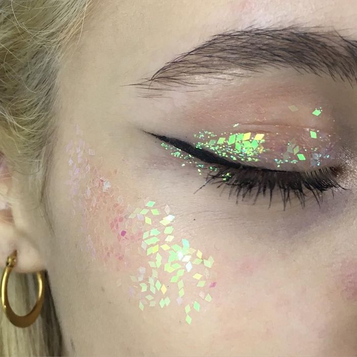 yellow and pale green, pink and silver, tiny diamond-shaped glitter pieces, decorating the eyelid and cheekbone, of a blond woman's face, make up ideas, black mascara and eyeliner