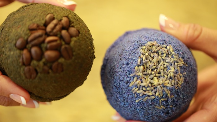 coffee beans covering a black bath bomb, held by woman's hand, with a classic french manicure, her other hand holds a textured, blue bath bomb, topped with dried lavender