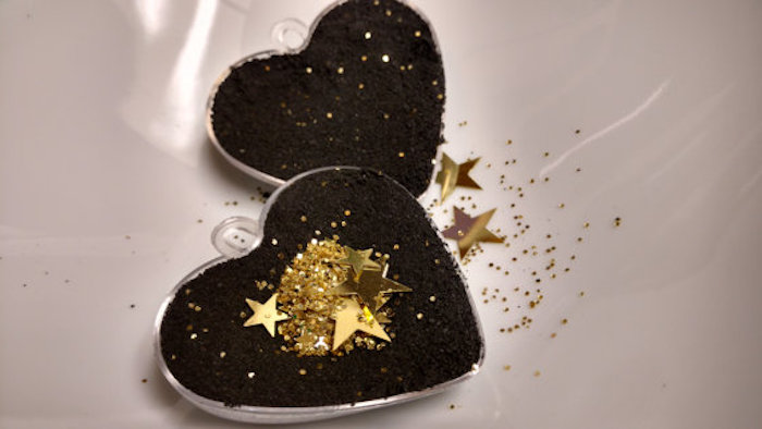 golden shiny star-shaped confetti, and glitter in the same color, inside a heart-shaped mould, filled with black powder, making a black bath bomb