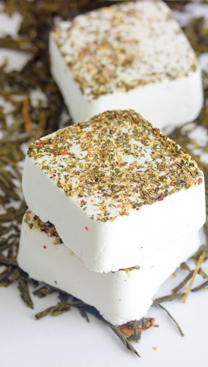 square white bath bomb tablets, in pure white, dusted with dried herbs, placed on white surface with more dried herbs