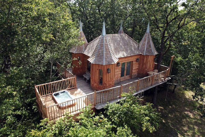 four tower-like wooden structures, attached to a castle-like tree house, built on a wooden platform, suspended over the ground, jacuzzi and a fence
