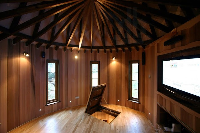 inside a tree house castle, round room with wood panelling on the walls, trap door and wooden beams on the ceiling, treehouse ideas, large TV and three windows