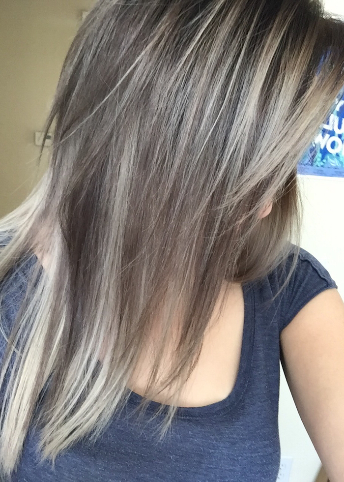 layered medium length hair, in mink brown, with light ash blonde streaks, light brown hair with blonde highlights, worn by young woman, in dark grey t-shirt