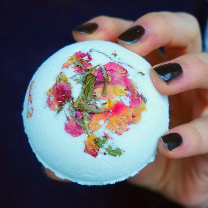 bath balls you can make at home, hand with black nail polish, holding pale blue bath bomb, decorated with dried rose leaves, and petals in yellow, orange and pink